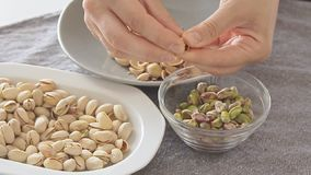 Woman hands opening pistachios above glass bowl. On the kitchen table filmed from high angle in slow motion video footage stock video footage