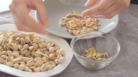 Woman hands opening pistachios above glass bowl. On the kitchen table filmed from high angle in slow motion video footage stock video
