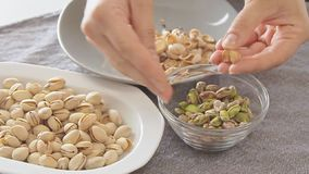 Woman hands opening pistachios above glass bowl. On the kitchen table filmed from high angle in slow motion video footage stock footage