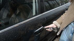 Woman hands opens the door of the car in close-up, sets in the car and closes the door. Woman hands opens the door of the dirty car in close-up, sets in the car stock video footage
