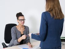 Woman hands over a document to another woman Royalty Free Stock Photos