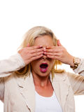 Woman with hands over eyes. A woman is standing with her hands over her eyes with her mouth open stock images