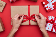Woman hands packing gift box isolated over red flat layout Royalty Free Stock Photos