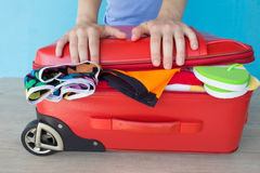 Woman hands packing her red suitcase. Open traveler& x27;s bag with clothing, accessories Stock Photo
