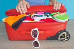 Woman hands packing her red suitcase. Open traveler`s bag with clothing, accessories Royalty Free Stock Images