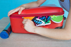 Woman hands packing her red suitcase. Open traveler`s bag with clothing, accessories Stock Photography