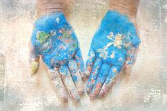 Woman hands in paint isolated on grunge background. Painted or smeared hands in blue.  stock photos