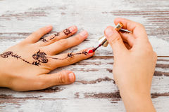 Woman Hands Painted with Black Henna Polishing the Nails Royalty Free Stock Image