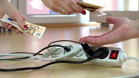 Woman hands pay euro banknotes for electricity usage in front of switch plugs. Woman hand count and pay euro money banknotes cash for electricity usage in front stock footage