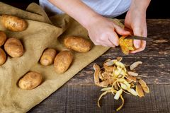 Woman hands peel potato, peelings on wooden cutting board. Three clean potatoes on plate. Cook clean the potatoes Royalty Free Stock Photography