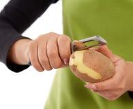Woman hands peeling potato Royalty Free Stock Photos