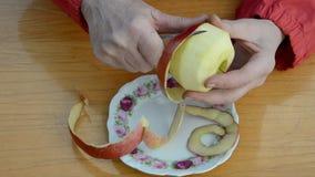 Woman hands peeling red apple stock footage