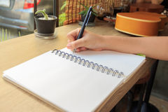 Woman hands with pen writing on notebook Stock Image