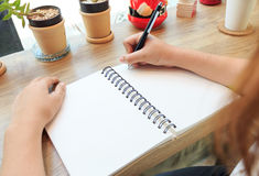 Woman hands with pen writing on notebook Stock Images