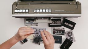 Woman hands picks an audio cassette tape from the table and place it in a retro player. Top view, closeup stock video