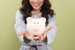 Woman hands with a piggy bank on a green background.  Stock Images