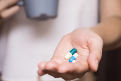 Woman hands with pills and Mug of water Royalty Free Stock Photo