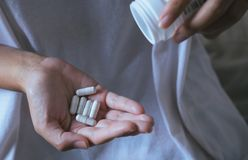 Woman hands with pills on spilling pills out of bottle,Female hand holding a medicine. Selective focus Royalty Free Stock Photography