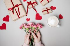 Woman hands with pink flower, gift box with heart and coffee on. White background. Valentine day, holiday background. Top view Stock Photography