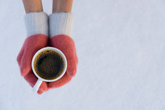 Woman hands in pink teal gloves holding a coffee mug on snow. Girl hands in pink teal gloves holding a coffee mug on snow Royalty Free Stock Photo