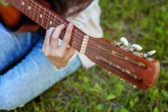 Woman hands playing acoustic guitar. Closeup of woman hands playing acoustic guitar on park or garden background. Teen girl learning to play song and writing stock images