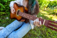 Woman hands playing acoustic guitar. Closeup of woman hands playing acoustic guitar on park or garden background. Teen girl learning to play song and writing stock photos