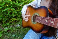 Woman hands playing acoustic guitar. Closeup of woman hands playing acoustic guitar on park or garden background. Teen girl learning to play song and writing royalty free stock photos