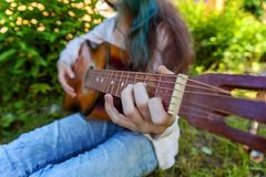 Woman hands playing acoustic guitar. Closeup of woman hands playing acoustic guitar on park or garden background. Teen girl learning to play song and writing royalty free stock images