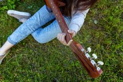 Woman hands playing acoustic guitar. Closeup of woman hands playing acoustic guitar on park or garden background. Teen girl learning to play song and writing royalty free stock photo