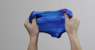 Woman hands playing with oddly satisfying blue slime gooey substance. Antistress royalty free stock photography