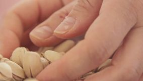 Woman hands playing with pistachios stock video