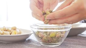 Woman hands playing with pistachios stock footage