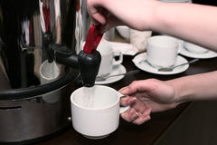 The woman hands pour hot water from the boiler Royalty Free Stock Image