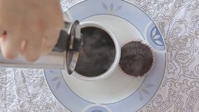 Woman hands pouring coffee on cup. Woman hands pouring hot steaming coffee on cup on the kitchen table filmed from above in slow motion video footage stock video footage