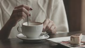 Woman hands pouring sugar to the cup in cafe. Close-up of a woman hands pouring sugar to the cup of coffee in cafe stock footage