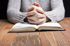 Woman hands praying with a bible in dark over Royalty Free Stock Image