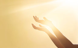Woman hands praying for blessing from god on sunset background. Woman hands praying for blessing from god on sunlight and sunset background royalty free stock image