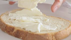 Woman hands preparing breakfast and spreading cheese cream. On bread slice film footage filmed in slow motion from low angle stock video