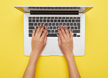 Woman hands printing in laptop standing on yellow background. Flat lay of woman hands printing in laptop standing on yellow background Royalty Free Stock Images