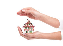 Woman hands protect little house on white Royalty Free Stock Images