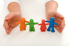 Woman hands protecting clay people family Royalty Free Stock Photo