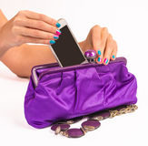 Woman hands putting cellphone to the clutch Royalty Free Stock Photography