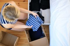 Woman hands putting clothes to donate box stock images