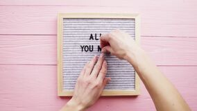 Woman hands putting phrase All You Need Is Love on gray letter board with black plastic letter, pink wooden background
