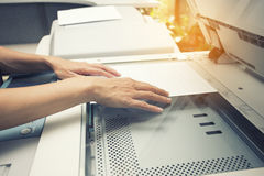 Woman hands putting a sheet of paper into a copying device. Close up stock image