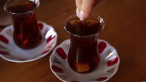 Putting sugar cubes inside the traditional turkish tea. Woman hands putting sugar cubes inside the traditional turkish tea on a wooden table stock video footage