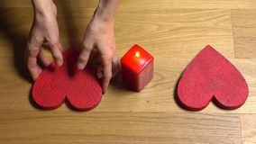 Woman hands putting two red heart shapes near candle. Love, romance, Valentine`s day, togetherness, family, date. Elegant female hands putting two red heart stock video