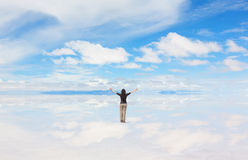 Woman with hands raised. Rear view of woman worshiping in nature, Salar de Uyuni, Bolivia Royalty Free Stock Photo