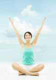 Woman hands raised up. Sitting in yoga lotus pose over sky backg Stock Photography