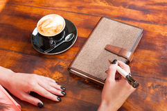 Woman hands ready to write outside on terrace table Royalty Free Stock Images